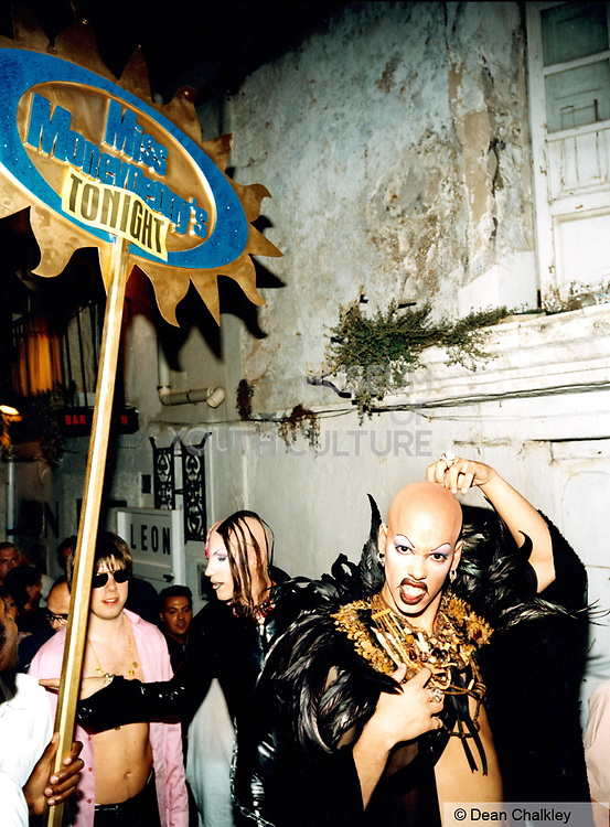 Transvestite clubber wearing a feather coat outside Miss Moneypenny's, Ibiza, 1999