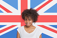 Portrait of young African American woman in white t-shirt smiling against British flag