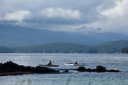 Sea kayakers enjoy calm waters and warm temperatures after a storm in the Broken Group Islands, BC