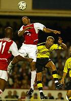 Photograph: Scott Heavey.<br />Arsenal v Aston Villa. FA Barclaycard Premiership match. 27/08/2003.<br />Thierry Henry beats Olof Mellberg in the air.