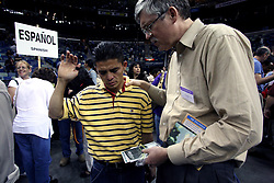 12 March 2006. New Orleans, Louisiana. <br /> Praising the Lord. A capacity crowd mingles with counselors in front of the pulpit at the last appearance from the Rev Billy Graham. Claiming this to be his last event preaching from the pulpit, the world's most famous evangelist, The Reverend Billy Graham addressed a capacity crowd at the New Orleans Arena as he brings his 'Celebration of Hope' weekend event to an end. After the show the counselors invite as many people as possible to invite Jesus into their hearts to be 'saved.' Proselytizing is intense. A migrant worker is 'saved' by a counselor.<br /> Photo©; Charlie Varley/varleypix.com