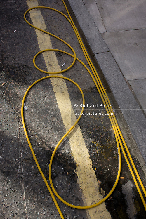 Coils and loops of yellow hosepipe on the ground in a south London street.