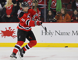 Jan 31, 2013; Newark, NJ, USA; New Jersey Devils defenseman Adam Larsson (5) shoots a puck during the warmups for their game against the New York Islanders at the Prudential Center.