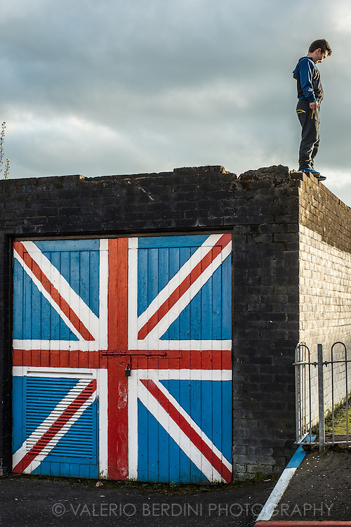 A teenager ready to jump off the roof of shed painted with the British flag in the loyalist area of Londonderry.