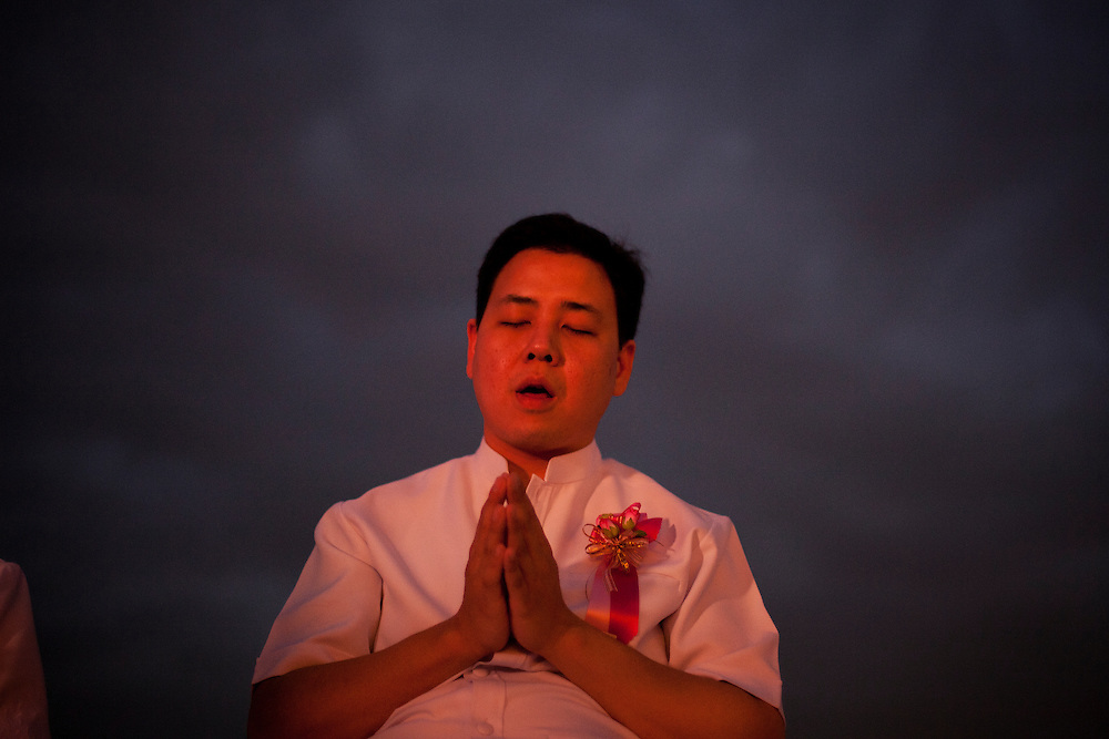 A devotee of the Dhammakaya Buddhist movement founded in Thailand pray during Makha Bucha day at Wat Phra Dhammakaya  on the outskirts of Bangkok, Thailand Wednesday, March 7, 2012.