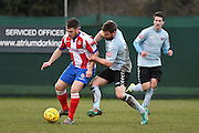 Dorking Wanderers Tom Tolfrey attacks against Lewes FC LLyon Cotton (C) during the Ryman League - Div One South match between Dorking Wanderers and Lewes FC at Westhumble Playing Fields, Dorking, United Kingdom on 28 January 2017. Photo by Jon Bromley.