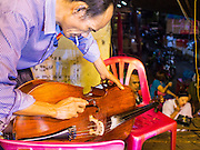 18 JANUARY 2015 - BANGKOK, THAILAND: A musician with the Sai Yong Hong Opera Troupe adjusts his cello before a performance at the Chaomae Thapthim Shrine, a Chinese shrine in a working class neighborhood of Bangkok near the Chulalongkorn University campus. The troupe's nine night performance at the shrine is an annual tradition and is the start of the Lunar New Year celebrations in the neighborhood. The performance is the shrine's way of thanking the Gods for making the year that is ending a successful one. Lunar New Year, also called Chinese New Year, is officially February 19 this year. Teochew opera is a form of Chinese opera that is popular in Thailand and Malaysia.             PHOTO BY JACK KURTZ