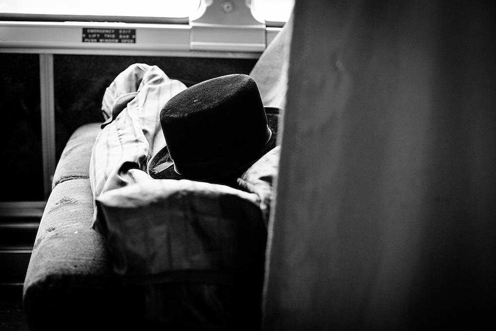 """Il cappello di tutti i giorni di un Chassidim posato sul sedile del bus che va a Monsey, New York nella parte destinata agli uomini dietro alla """"mechiza"""" la spartizione. Foto scatata il 16 Febbraio, 2014."""
