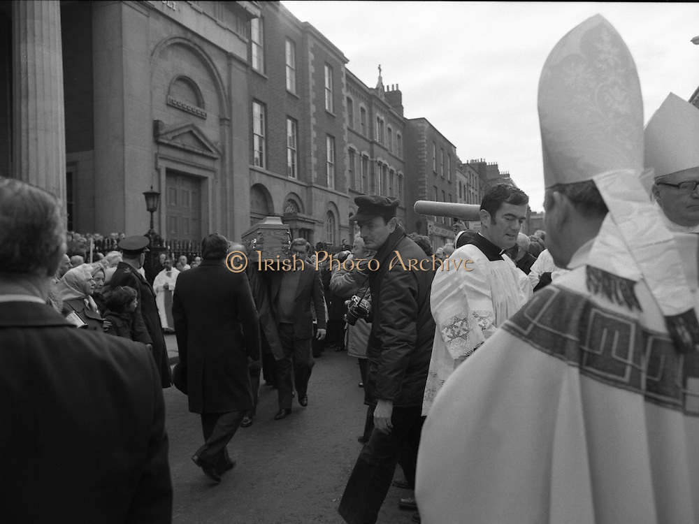 Funeral Of Frank Duff.   (N50)..1980..13.11.1980..11.13.1980..13th November 1980..The Solemn Funeral Mass for Frank Duff, founder of The Legion of Mary,was concelebrated with his Eminence,Cardinal Tómas O'Fiaich,Archbishop of Armagh and Primate of All Ireland as principal celebrant, at St Andrew's Church, Westland Row,Dublin. The funeral took place after the mass to Glasnevin Cemetery..Image of the coffin being borne by Legionaries as it is carried to the waiting hearse. Cardinal O'Fiaich is in the foreground waiting for the final blessing.