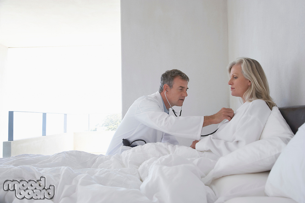 Doctor doing house call on mature woman in bed using stethoscope side view