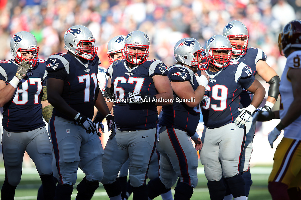 The New England Patriots offensive line breaks from the huddle and heads to the line of scrimmage during the 2015 week 9 regular season NFL football game against the Washington Redskins on Sunday, Nov. 8, 2015 in Foxborough, Mass. The Patriots won the game 27-10. (©Paul Anthony Spinelli)