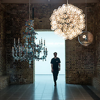 London, UK - 15 September 2014: A member of the staff walks under pendant lamps by Cerith Wyn Evans including 'Taraxacum 2014' (Center, illuminated) during the press preview of his new solo exhibition at Serpentine Sackler Gallery.