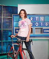 Susie Dent photographed on on the Countdown TV set in front of letters board. Susie Dent is wearing a woman against Cancer T Shirt and is leaning over a professional racing cycle