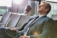Mature businessman sleeping while listening to music with earphones on in airport with lens flare