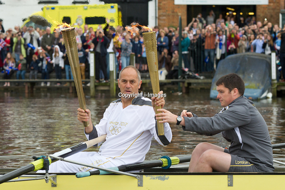Five time gold medal winner Sir Steve Redgrave rows The Olympic Torch  along the River Thames at Henley , Oxon on Day 53 of the relay.  Tuesday 10  July  2012.  Henley, UK..Photo by:/i-Images.