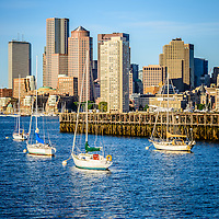 Boston skyline photo with Port of Boston pier, downtown Boston skyscrapers, and sailboats.