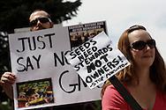 """Una manifestante porta una cartulina con el mensaje """"Las semillas necesitan quienes las cuiden, no duenos.  Paremos a Monsanto"""".  El 25 de mayo de 2013, centenares de personas salieron a las calles de Denver a manifestarse en contra de la corporacion Monsanto, productora de herbicidas y semillas geneticamente modificadas, entre otros.  Esta accion se realizoD en mas de 400 ciudades en mas de 50 paies alrededor del mundo. Photo: Graham Charles/Imagenes Libres."""