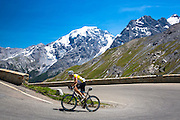 Cyclist rides Scott British roadbike uphill on The Stelvio Pass, Passo dello Stelvio, Stilfser Joch, in the Alps, Italy