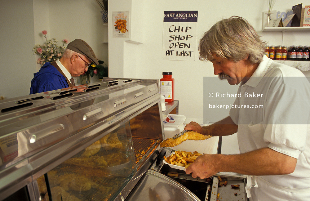 A chip shop owner serves up some battered fish and chips to a customer in 'Nice Fish and Chips' on Old Road, the first fish and chip business in the conservative Essex seaside town of Frinton-on-Sea, on 26th June 1992, in Frinton, England.