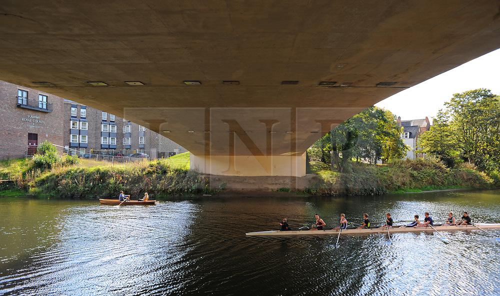 © Licensed to London News Pictures. <br /> 24/09/2014. <br /> <br /> Durham, United Kingdom<br /> <br /> A Durham University boat crew pass a couple in a rowing boat as they pass under a bridge on the River Wear in Durham City.<br /> <br /> <br /> Photo credit : Ian Forsyth/LNP