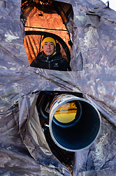 Wildlife photojournalist Noppadol Paothong poses for a photo in his blind in southwest Wyoming. ©John L. Dengler / DenglerImages.com