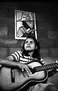 Young girl learning the guitar. Music For Hope community music project, Bajo Lempa, El Salvador.<br /> 1999