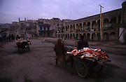 Butchers bring meat to sell in Kashgar's Sunday Market