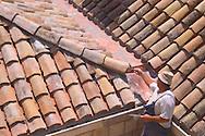 A roofer repairing a terracotta roof in<br /> Dubrovnik old town, Croatia<br /> c. Ellen Rooney
