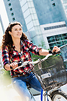 Portrait of young beautiful woman smiling while riding bicycle in the middle of the city with lens flare in background