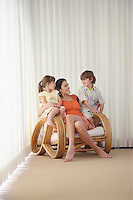 Mother with son (7-9) and daughter (5-6) sitting in armchair