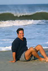 man sitting on the beach in shorts and a shirt