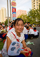 Pyongyang, North Korea. A young Pioneer waiting for the parade on September 9th, in Pyongyang carrying a Mickey Mouse fan. She didn't know anything about the cartoon character<br /> -Do you know the name of this cartoon character on the fan?<br /> -No Mr Eric. It's just a mouse. It&rsquo;s Chinese!