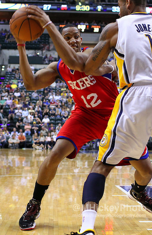 March 14, 2012; Indianapolis, IN, USA; Philadelphia 76ers shooting guard Evan Turner (12) tries to break the pressure of Indiana Pacers shooting guard Dahntay Jones (1) at Bankers Life Fieldhouse. Mandatory credit: Michael Hickey-US PRESSWIRE