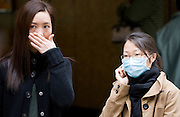 Young Chinese women with covered mouths in Hong Kong, China