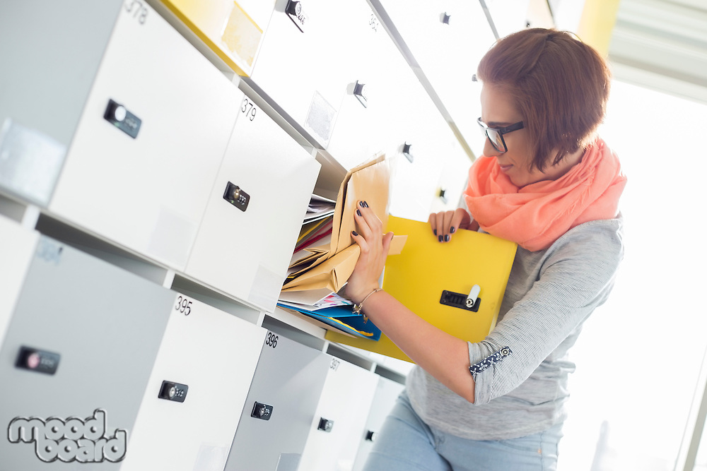 Young businesswoman removing file from locker at creative office