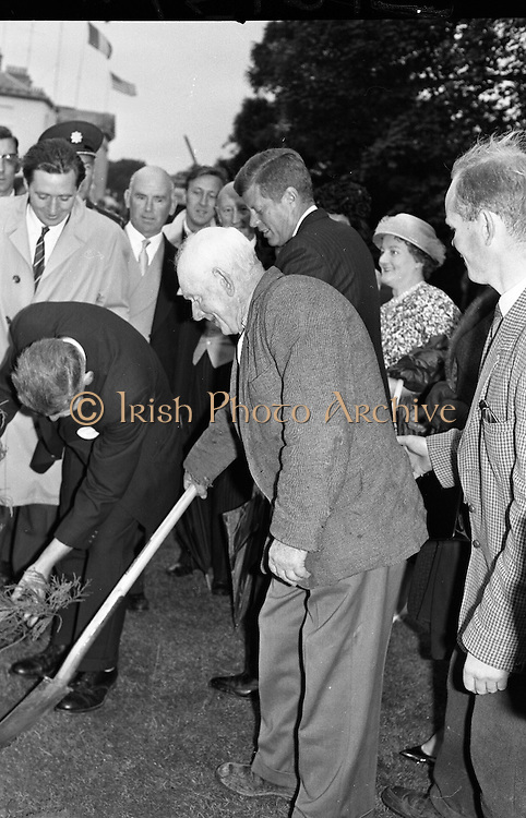 President John F. Kennedy attends aGarden Party at Aras an Uachtarain.  Kennedy plants a Californian Redwood in the grounds of the residence, watched by President de Valera and Mr. Frank Aiken, Minister for External Affairs (left)..27.06.1963