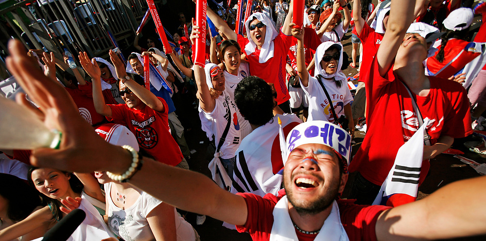 Frankfurt | Deutschland 13.06.2006:  In der Innenstadt Frankfurts schauen s&uuml;dkoreanische Fu&szlig;ballfans das Spiel ihrer Mannschaft gegen Togo und feiern nachher den Sieg ihrer Mannschaft.<br /> <br /> hier: S&uuml;dkoreanische Fans feiern den Sieg ihrer Mannschaft gegen Togo.<br /> <br /> Sascha Rheker<br /> 20060613<br /> <br /> [Inhaltsveraendernde Manipulation des Fotos nur nach ausdruecklicher Genehmigung des Fotografen. Vereinbarungen ueber Abtretung von Persoenlichkeitsrechten/Model Release der abgebildeten Person/Personen liegt/liegen nicht vor.]