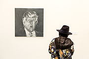 New York, NY - 5 May 2017. The opening day of the Frieze Art Fair, showcasing modern and contemporary art presented by galleries from around the world, on Randall's Island in New York City. A woman visitor looks at a painting of a screaming president-elect Donald Trump by Yan Pei-Ming in the Galerie Thaddaeus Ropac.