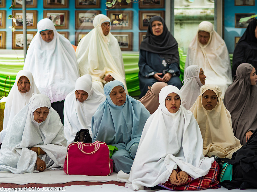 06 JULY 2016 - BANGKOK, THAILAND:  Women wait for Eid services to start at Ton Son Mosque in the Thonburi section of Bangkok. Eid al-Fitr is also called Feast of Breaking the Fast, the Sugar Feast, Bayram (Bajram), the Sweet Festival or Hari Raya Puasa and the Lesser Eid. It is an important Muslim religious holiday that marks the end of Ramadan, the Islamic holy month of fasting. Muslims are not allowed to fast on Eid. The holiday celebrates the conclusion of the 29 or 30 days of dawn-to-sunset fasting Muslims do during the month of Ramadan. Islam is the second largest religion in Thailand. Government sources say about 5% of Thais are Muslim, many in the Muslim community say the number is closer to 10%.       PHOTO BY JACK KURTZ