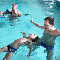 Nederland, Amsterdam, 11 juli 2015.<br /> Steeds meer kinderen krijgen een turbocursus zwemmen. Swimbee in Amsterdam traint momenteel een groep kinderen die dertien aaneengesloten dagen les krijgen<br /> Op de foto: zweminstructeur Mike de Bruijn met Hero in het zwembad van het Ronald Mc Donald Centre,<br /> <br /> <br /> Foto: Jean-Pierre Jans