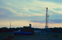 Stock photo of men loading hay into the back of a pickup truck near an on-shore drilling site