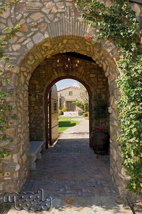 Outside archway with an open gate revealing part of a house in the distant
