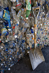 Stanford Recycling center. Compacted plastic bottles with shovel.
