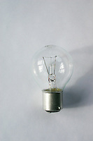 Clear electric light bulb, push-in fitting, against plain background<br />