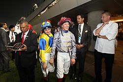 Jockeys Lanfranco Dettori (C) and Andrea Atzeni (in yellow) walk out to the parade ring ahead of their race, the Dubai Sheema Classic, during the Dubai World Cup, at the Meydan in Dubai, United Arab Emirates, Saturday March 29, 2014. With a total prize purse of US$27.25 million, the 19th running of Dubai World Cup is the world's richest day of racing. Picture by Randi Sokoloff / i-Images