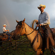 As a rainbow appears on the horizon, Michael Flattery waits for cattle to be herded into a corral where calves will be seperated for bi-annual vaccinations, branding, the implant of growth stimulants, and in some cases, castration, at the Bar B ranch near Albia, Iowa.  After a morning rain, muddy conditions made the task more difficult.  Ranch owner Catherine Bay runs the operation with a herd of over 2,000 cattle.