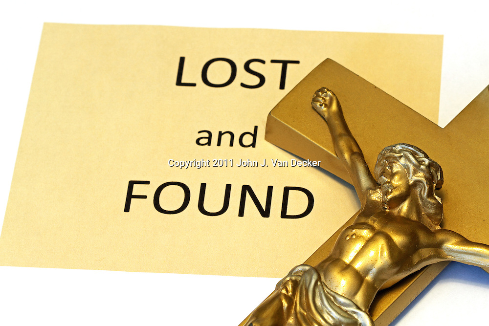 A Crucufix next to a Lost and Found sign. Conceptual image regarding faith.