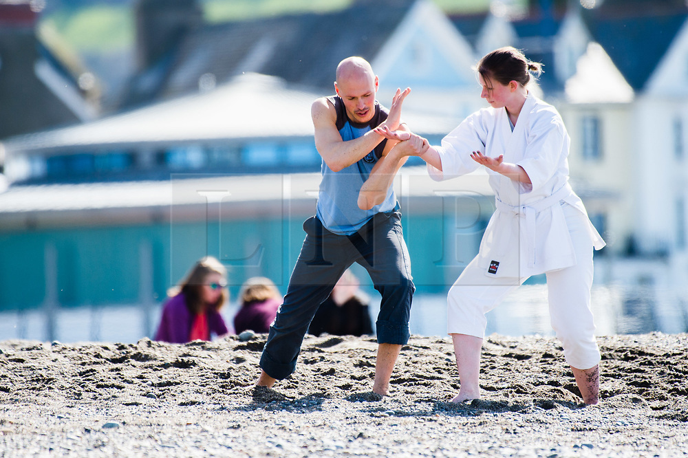 © London news pictures. 25/03/2017. Aberystwyth, UK.<br /> Aberystwyth university students practicing their Aikido moves on the beach on an afternoon of glorious sunshine and clear blue skies in Aberystwyth on the west wales coast, with temperatures expected to reach 18 or 19ºc by the afternoon. Sheltered from the cooling effects of an easterly wind, West Wales is expected to be the warmest pace in the UK today (Sat). Photo credit: Keith Morris/LNP