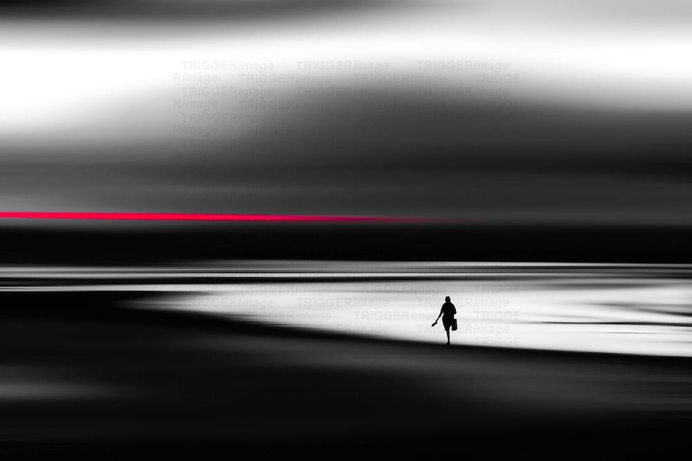 Conceptual beach scene with lone figure walking across sand