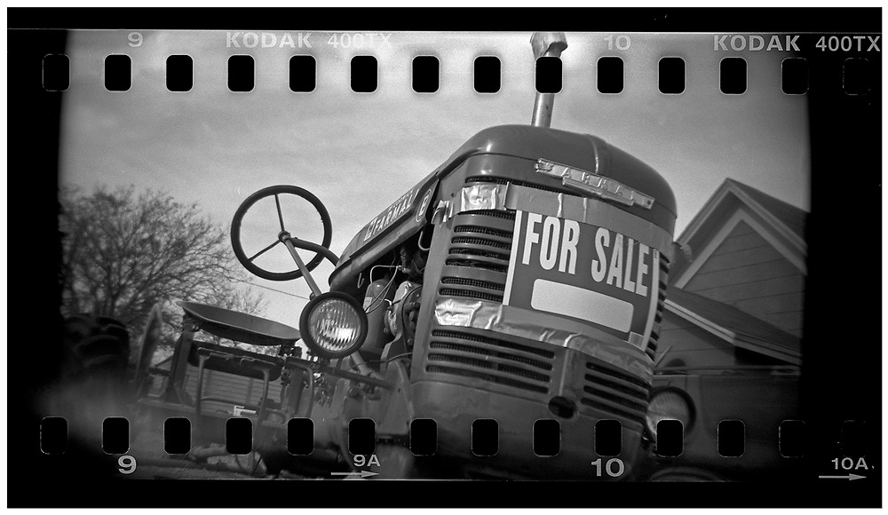 """A tractor is posted with a """"for sale"""" sign on a lawn in Crawford, Texas, December 13, 2008. Bush moved to the small Texas town, population 705, in 1999 during his run for the presidency in 2000. The effect of the image was achieved by shooting 35mm black and white film in a medium format camera thereby exposing the entire negative including the sprocket holes of the film. REUTERS/Jim Young"""